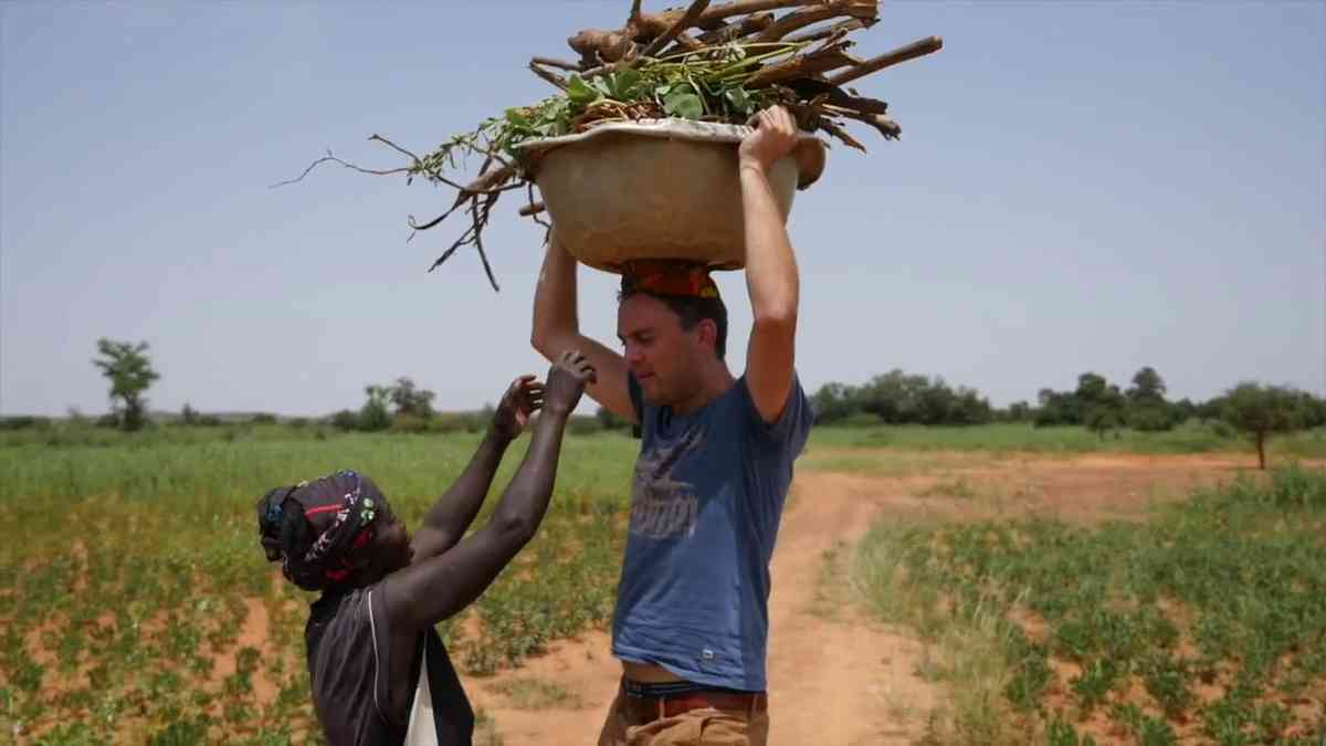 Pieter helping local farmers carry firewood in Burkina Faso